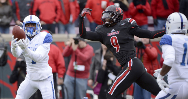 Nov 29, 2014; Louisville, KY, USA; Kentucky Wildcats safety A.J. Stamps (1) intercepts a pass intended for Louisville Cardinals wide receiver DeVante Parker (9) during the first quarter at Papa John's Cardinal Stadium. Mandatory Credit: Jamie Rhodes-USA TODAY Sports