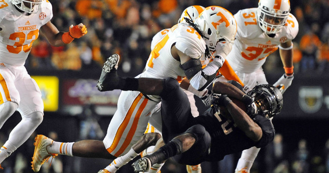 Nov 29, 2014; Nashville, TN, USA; Vanderbilt Commodores running back Ralph Webb (26) is stopped after a short gain by Tennessee Volunteers linebacker Jalen Reeves-Maybin (34) during the second half at Vanderbilt Stadium. The Volunteers won 24-17. Mandatory Credit: Christopher Hanewinckel-USA TODAY Sports