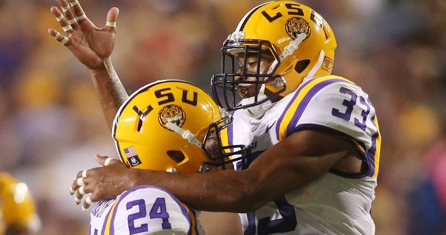 Oct 18, 2014; Baton Rouge, LA, USA; LSU Tigers safety Jamal Adams (33) and LSU Tigers defensive back Ed Paris (24) celebrate a tackle against the Kentucky Wildcats in the first quarter at Tiger Stadium. Mandatory Credit: Crystal LoGiudice-USA TODAY Sports