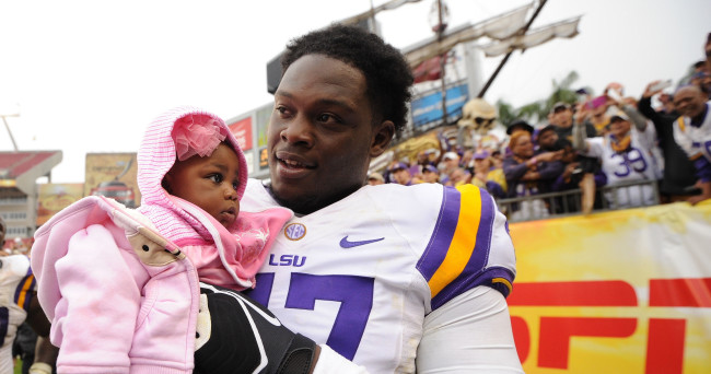 Jan 1, 2014; Tampa, Fl, USA; LSU Tigers defensive tackle Maquedius Bain (47) holds a small child after defeating the Iowa Hawkeyes at Raymond James Stadium. Mandatory Credit: Steve Mitchell-USA TODAY Sports