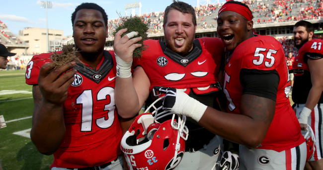 Nov 28, 2015; Atlanta, GA, USA; Georgia Bulldogs defensive end Jonathan Ledbetter (13), center Hunter Long (66, center), and guard Dyshon Sims (55) celebrate with a piece of the field after their win against the Georgia Tech Yellow Jackets at Bobby Dodd Stadium. The Bulldogs won 13-7. Mandatory Credit: Jason Getz-USA TODAY Sports
